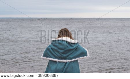 Woman In Costume With Cape. Adult Woman With A Mantle Standing On The Seashore. Windy Weather