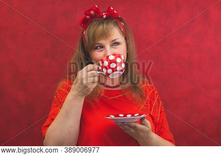 Woman In Red Posing On The Red Background. Spotted Cup With Saucer In The Hands