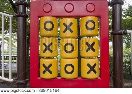 Yellow Plastic Details With X And O Symbols Of Mechanical Noughts And Crosses Game On Playground.