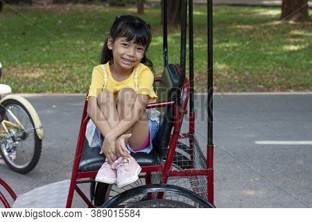 Asian Little Girl Sitting On A Tricycle Happily On Vacation Holiday.
