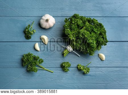 Fresh Curly Parsley And Garlic On Blue Wooden Table, Flat Lay