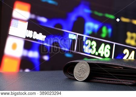A Quarter Of Us Dollar Coins On Obverse (usd) And Black Wallet On Black Floor With Digital Board Of