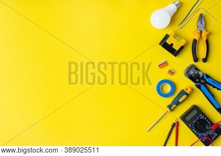 Different Electrician's Supplies On Yellow Background. Background Of Professional Electrician Tools
