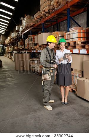 Happy young female supervisor and foreman using digital tablet at warehouse