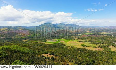 Fertile Farmlands With Growing Crops And Mountains With Clouds Against A Blue Sky. Mindanao, Philipp