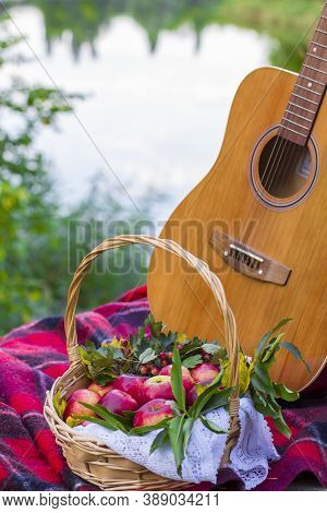 Picnic In Nature. Picnic Near River. Guitar And Red Apples In Wicker Basket On Plaid Blanket Near Ri