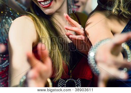 Young people dancing in club or disco and have party; the girls and boys, friends, having fun poster