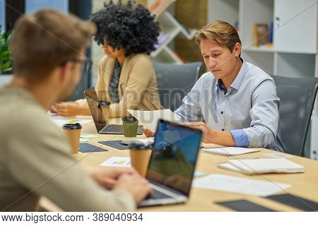 Office Life. Three Young Multiracial Business People Sitting At Desk In The Board Room And Working O