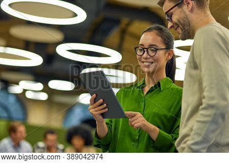 Young Cheerful Asian Woman Showing Something On Digital Tablet To Her Male Colleague While Standing