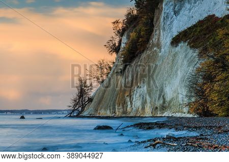 Chalk Cliffs In The Morning On The Island Of Ruegen. Autumn Coastline At Sunrise. Trees And Stony Co
