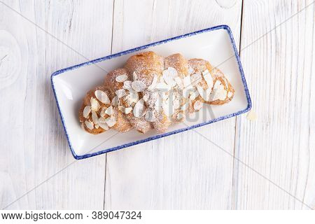 Croissant In A Plate On A Light Board.