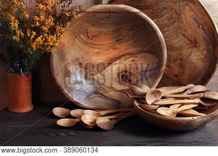 Handmade Wooden Utensils On The Kitchen Table. Wooden Plate, Bowl, Dishes And Spoons On The Table