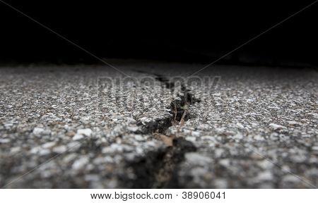 Cracked road on asphalt close up