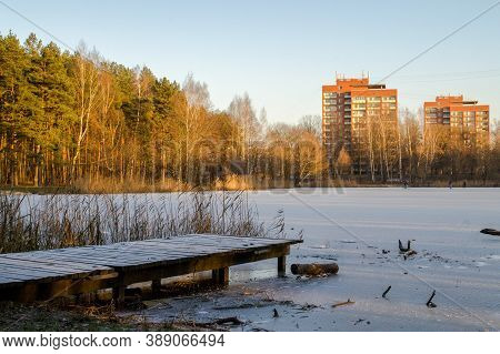 Morning By The Lake In The Winter. Lake Near Forest And With Tall Brick Houses In The Background. An