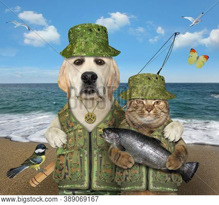 A Dog Fisher With A Fishing Rod Hugs A Cat With Big Fish On A Beach Of The Sea.