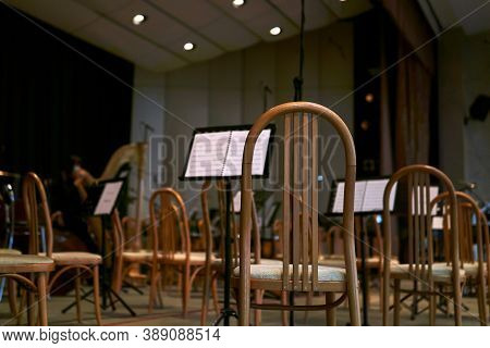 Empty Concert Hall Stage With Chairs And Musical Scores Before A Symphony Orchestra Performance