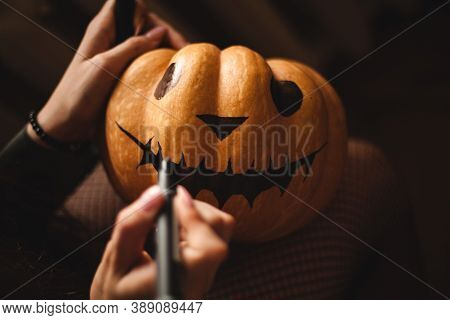 A Cute Young Girl Is Sitting At A Table In The Living Room Painting Her Face On A Big Pumpkin For Ha