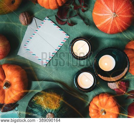 Top View Orange And Green Decorative Pumpkins, Apples, Nuts, Candles And Blank Postcard With Envelop