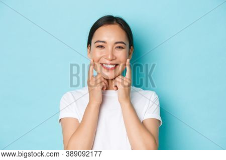 Close-up Of Beautiful Asian Girl Looking Pleased, Smiling White Teeth, Touching Cheeks, Recommend Sk