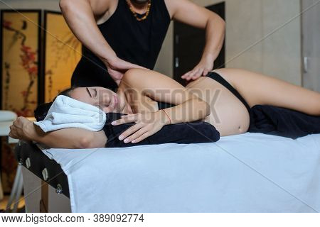 Later View Of Pregnant Caucasian Young Woman Lying On A Bed And Having A Relaxing Oriental Prenatal