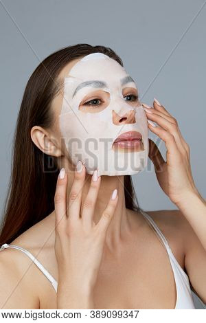 Beauty Face Skin Care. Woman Apply A Cloth Moisturizing Mask On Face . Girl Model With Cosmetic Mask