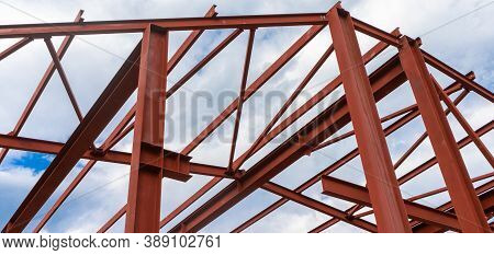 Red Metal Structure Against The Sky. Metal Frame Of A Building, Hangar Or Production Facility.