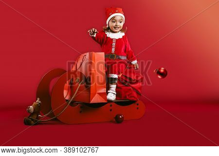 Merry Christmas And Happy New Year. Little Girl Like To Ride Sleigh By Xmas Decorations With Reindee