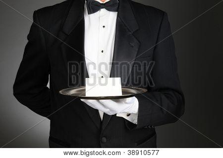 Un mayordomo con un esmoquin con una tarjeta de nota en una bandeja de plata delante de su torso. El hombre es unrecog
