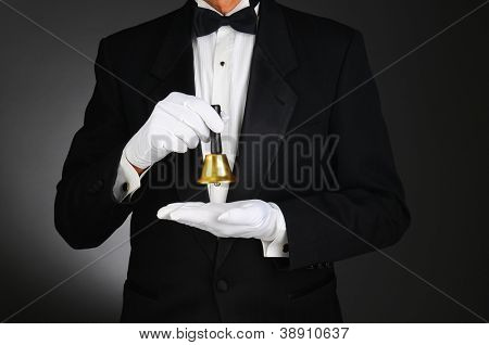 Closeup of a butler wearing a tuxedo and holding a service bell in front of his torso. Man is unrecognizable. Horizontal format on a light to dark gray background.