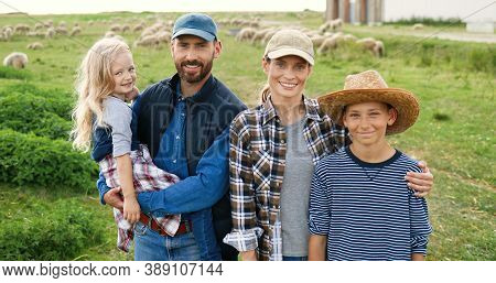 Portrait Of Caucasian Happy Family With Little Kids Standing At Pasture With Sheep Flock On Backgrou