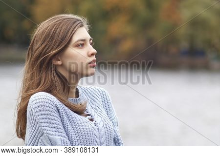Profile Side Portrait Of Serious Pensive Thoughtful Young Woman In The Autumn Park Near Lake In Knit
