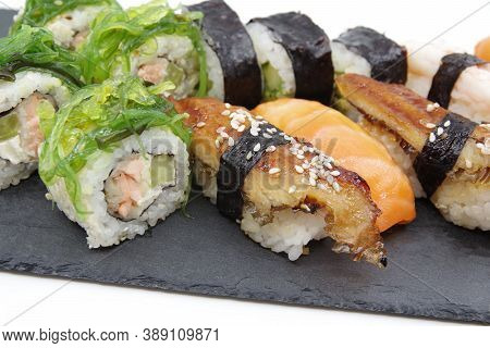 Japanese Sushi Food On A Black Tray, Served With Ginger, Soy Sauce And Seaweed Salad. Sushi Rolls, S