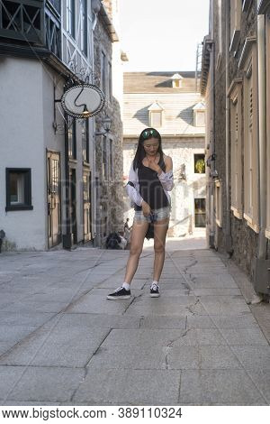A Chinese Woman Standing In A Narrow Alleyway Near The Place Paris In The Old Port Area Of Quebec Ci
