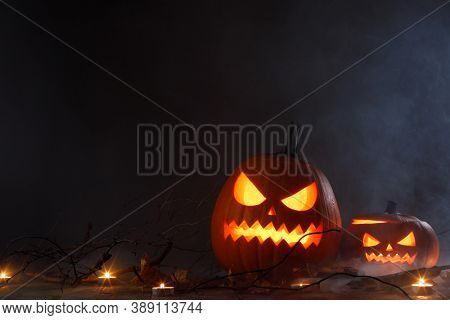 Halloween pumpkins head jack o lantern, candles and dry maple leaves in mist