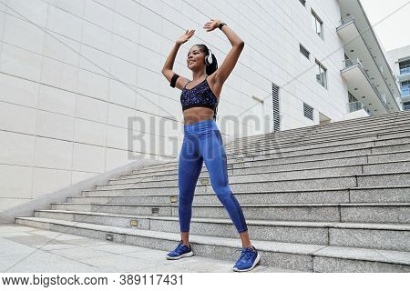 Smiling Fit Young Black Woman Doing Jumping Jacks Exercise Outdoors