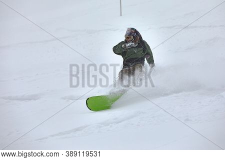 VAL D'ALLOS, FRANCE -CIRCA 2018: Young snowboarder coming down fast in fresh powder snow off-piste free ride. Plowing snow in a turn