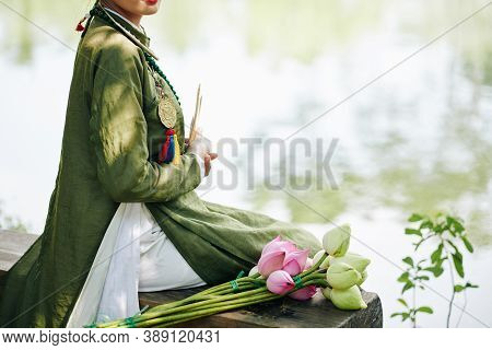 Cropped Image Of Young Woman In Ao Dai Dress Sitting On Bench Next To Pink And White Lotus Flowers