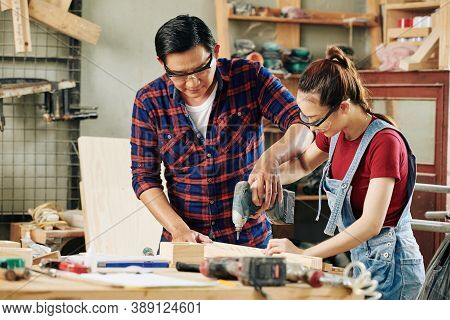 Carpenter In Goggles Teaching Female Apprentice Working With Electric Drill When Making Furniture In