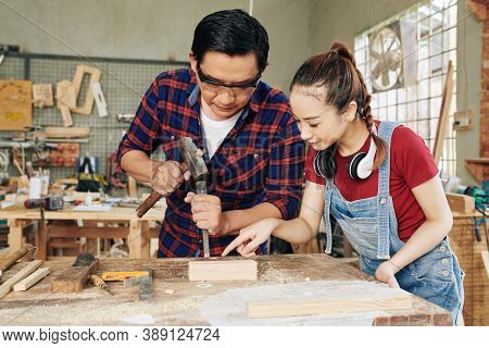 Profesional Serious Asian Carpenter Showing Apprentice How To Carve Wood