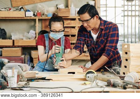 Experienced Carpenter Helping Apprentice To Polish Wooden Crates With Sander Hand Tool
