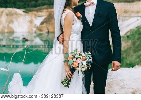 Newly Married Loving Couple With Rings On Their Hands And A Bouquet Of The Bride Hugging.