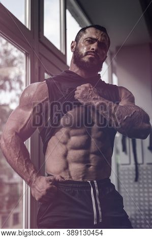 Strong Young Caucasian Man Athlete With Beard Showing His Perfect Physique Abdominal Muscle Near Win