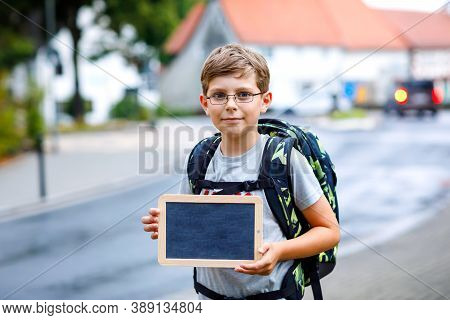 Happy Little Kid Boy With Glasses And Backpack Or Satchel. Schoolkid On The Way To Middle Or High Sc