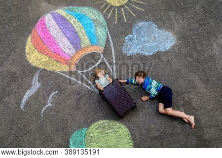 Happy Little Toddler Girl And Kid Boy Flying In Hot Air Balloon Painted With Colorful Chalks In Rain