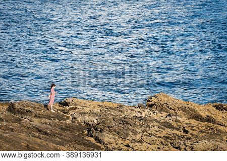 Portonovo, Spain - August 15, 2020: A Young Woman Checks Her Smartphone While Enjoying The Sunset On