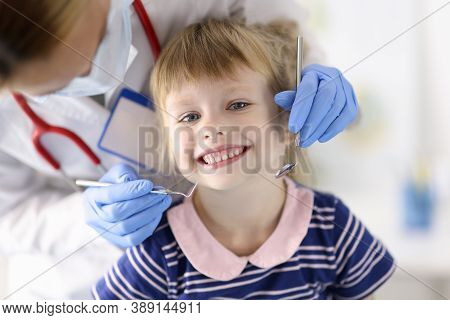 Dentist Doctor Examines Teeth Of Little Smiling Girl In Clinic. Painless Dental Treatment For Childr