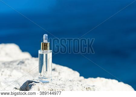 Cosmetic Serum In Transparent Glass Dropper Bottles On Natural Stone. Blue Sea Background, The Conce