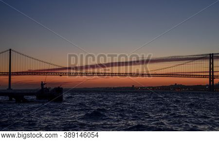 The 25th Of April Suspension Bridge Over The Tagus River, At Sunset, In Lisbon, Portugal.