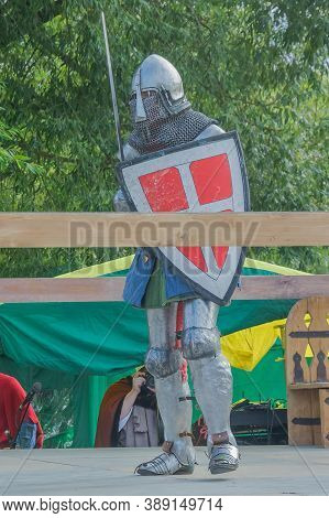A Knight In Heavy Medieval Armor Prepares To Fight An Opponent With Swords. Protected By An Iron Hel