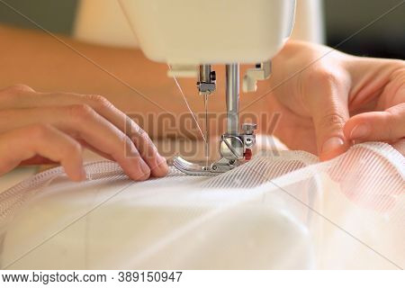 The Process Of Sewing Curtains From A Mesh Of White Fabric. The Rolled Edge Of The Fabric Is Placed